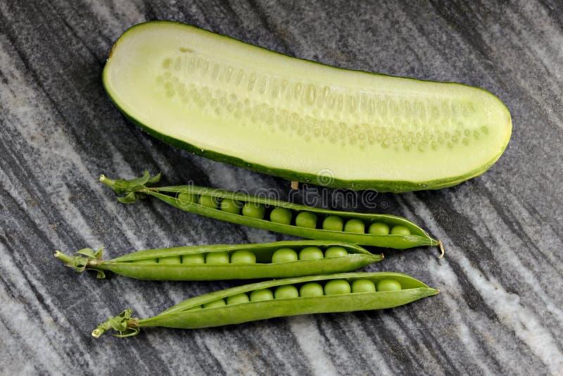 Drie peulen van groene erwten en komkommer op een granietplaat stock fotografie