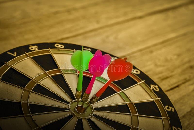 Drie Pijltjepijl die in het doelcentrum raken van dartboard stock foto's