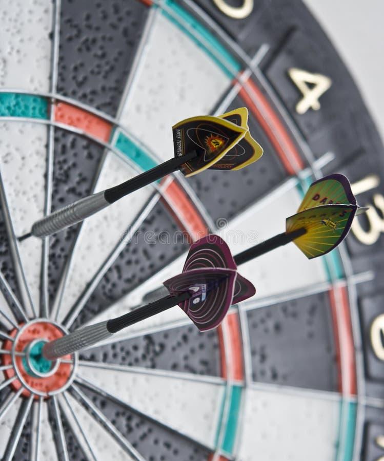 Drie pijltjes in dartboard stock afbeelding