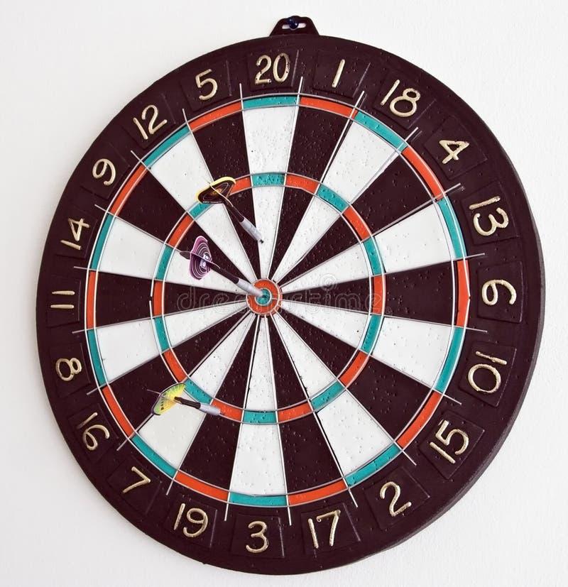 Drie pijltjes in het dartboard stock afbeelding