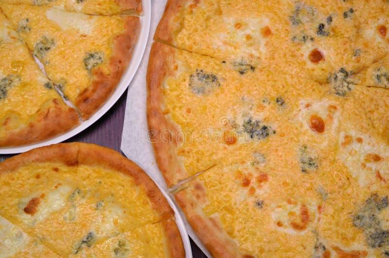 Drie pizza's met vier soorten kaas van verschillende grootte op een donkere achtergrond royalty-vrije stock fotografie