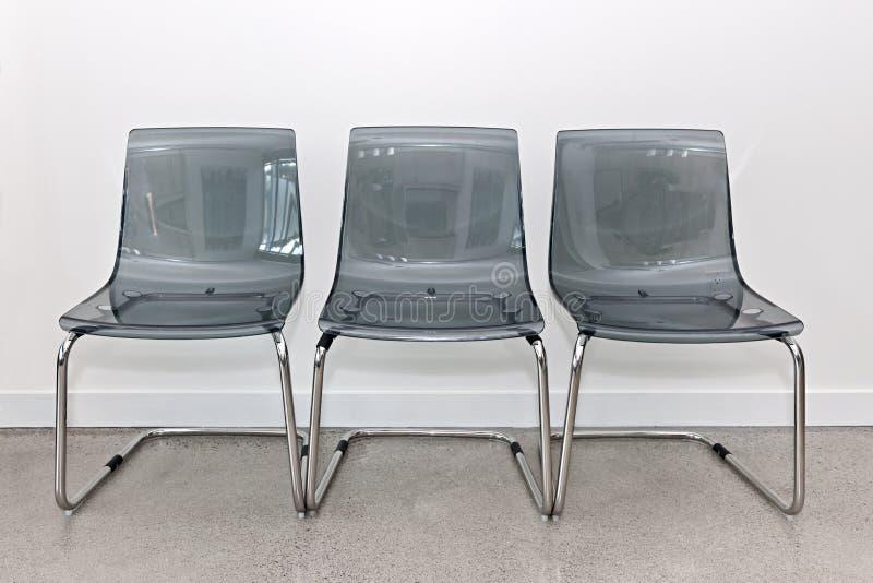 Drie plastic stoelen tegen muur stock afbeelding