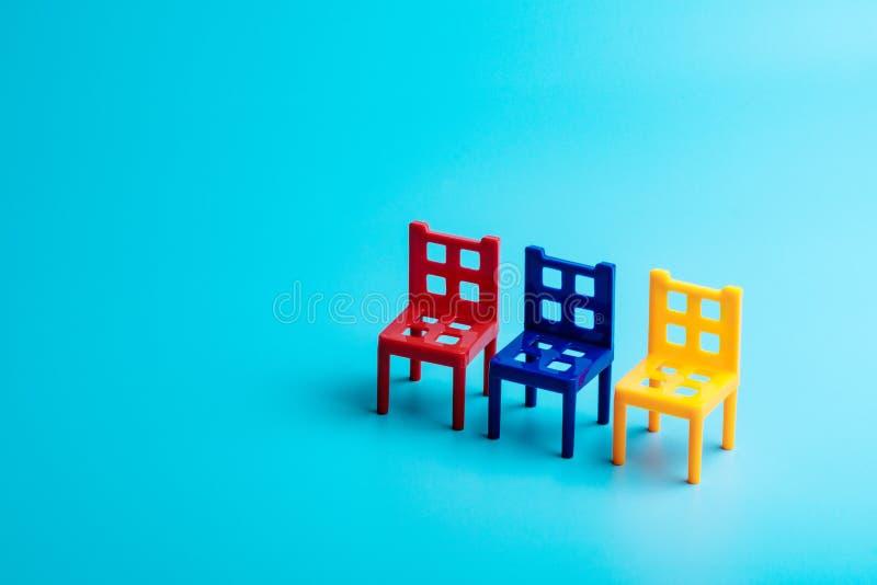 Drie plastic stuk speelgoed stoelen van verschillende kleuren stock fotografie
