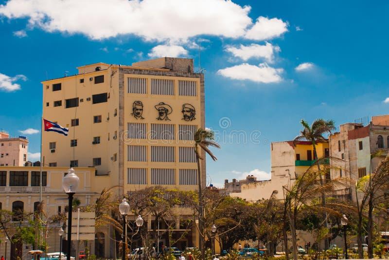 Drie portretten zijn op de muur van het gebouw: Che Guevara, Fidel Castro De Cubaanse vlag ontwikkelt zich cuba havana stock afbeelding