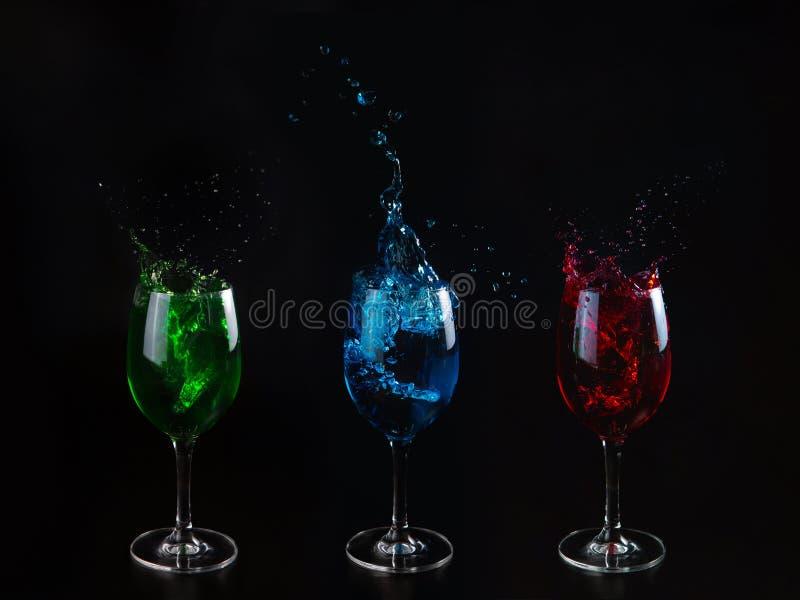 Drie primaire kleuren: rood, groen, blauw Glazen met multicolored water op een zwarte geïsoleerde achtergrond Bespattend water royalty-vrije stock foto