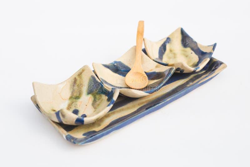 drie putten van ceramisch steengoed en houten lepels met witte achtergrond stock foto