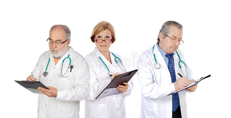 Drie rijpe artsen die de rapporten invullen stock foto's