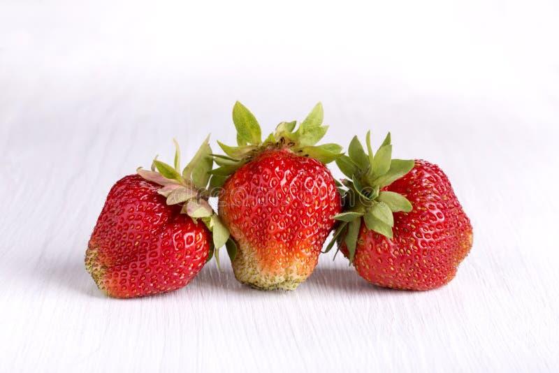 Drie rijpe rode aardbeien op wit houten bord stock foto