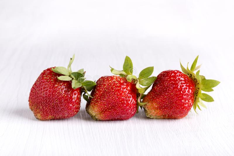 Drie rijpe rode aardbeien op wit houten bord stock afbeelding