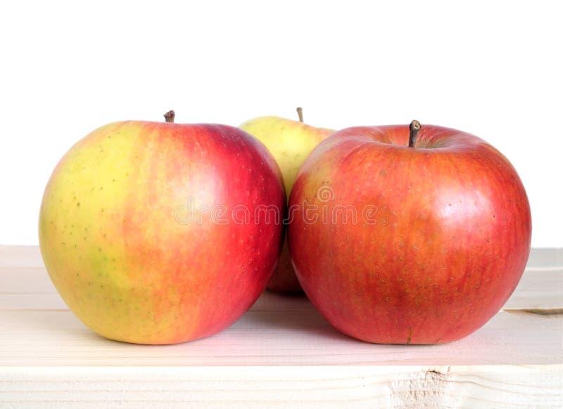 Drie rijpe rode appelen in beige houten plankenclose-up royalty-vrije stock foto's