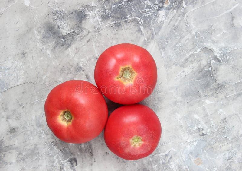 Drie rijpe tomaten op een grijze concrete achtergrond Hoogste mening stock foto