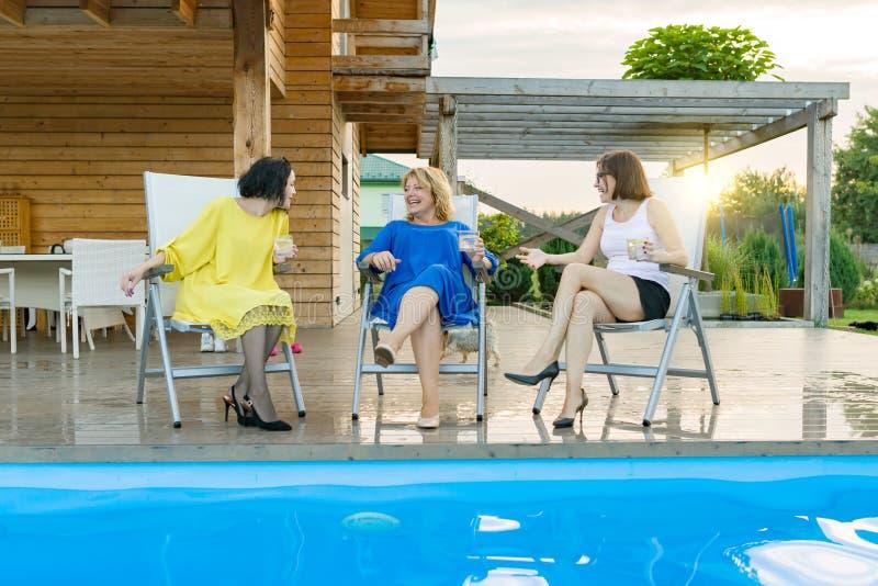 Drie rijpe vrouwen op middelbare leeftijd hebben pret en het spreken, zittend in een lanterfanter door de pool, de zomeravond stock fotografie
