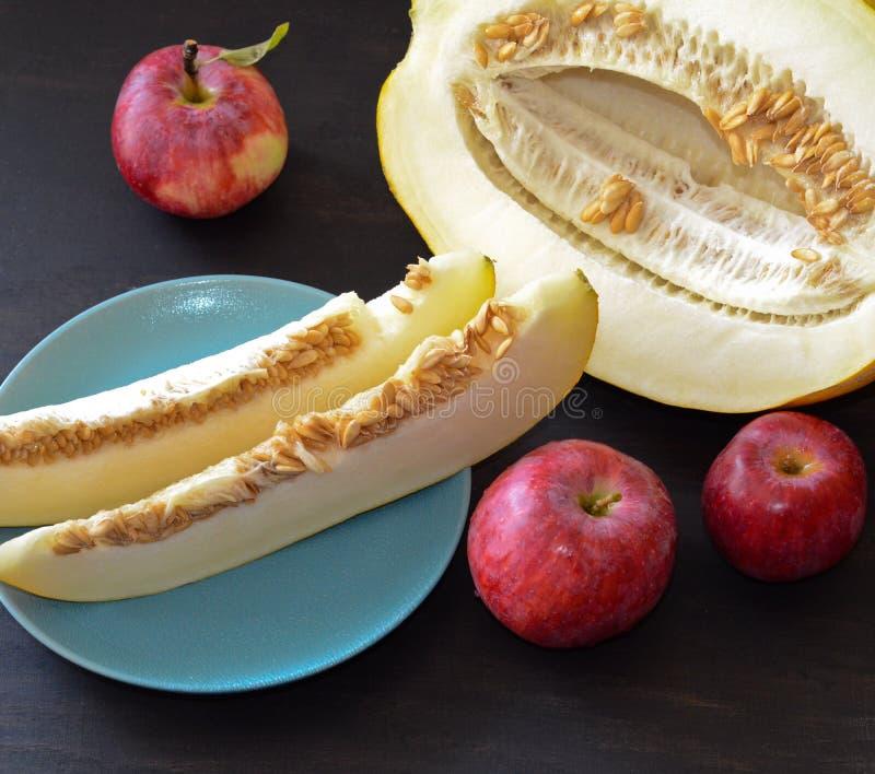 Drie rode appelen en stukken van meloen op de plaat en gesneden de meloen bloeien naast Astra stock foto