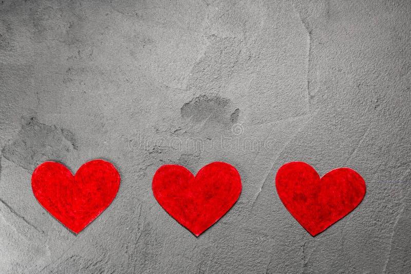 Drie Rode document harten op grijze muur met exemplaarruimte royalty-vrije stock afbeeldingen