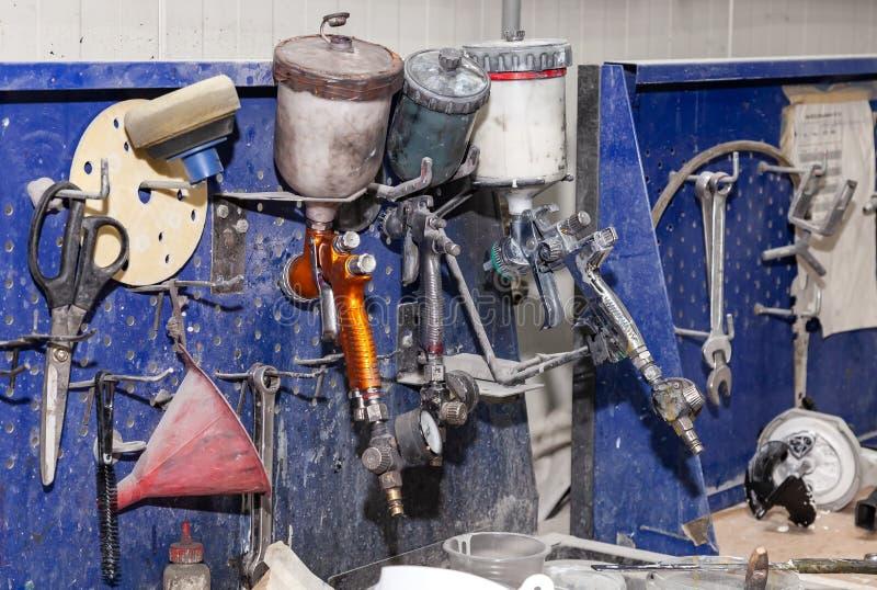 Drie rode het kanonspuitbus van de lichaamsverf en blauw op een werkbank in een workshop van de voertuigreparatie naast een ander royalty-vrije stock foto