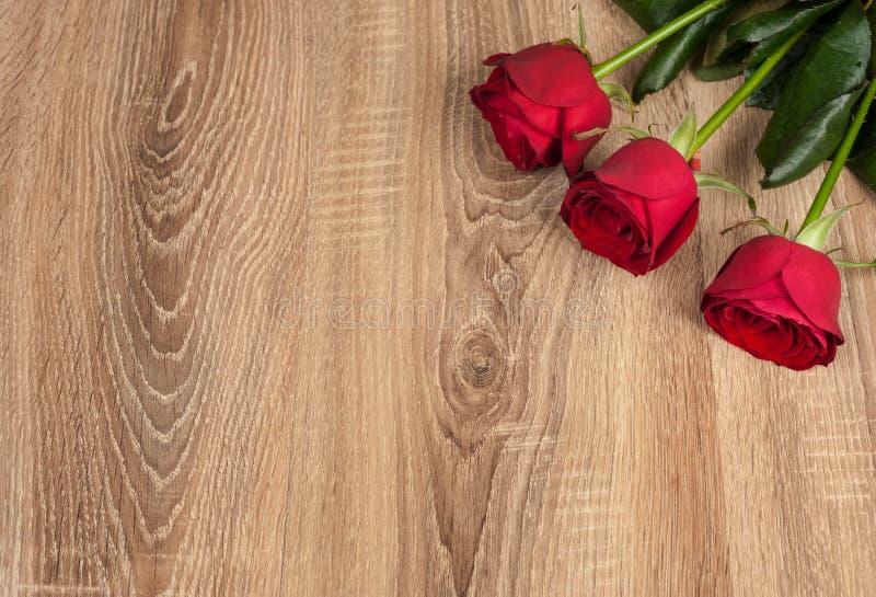 Drie rode rozen op hout royalty-vrije stock foto