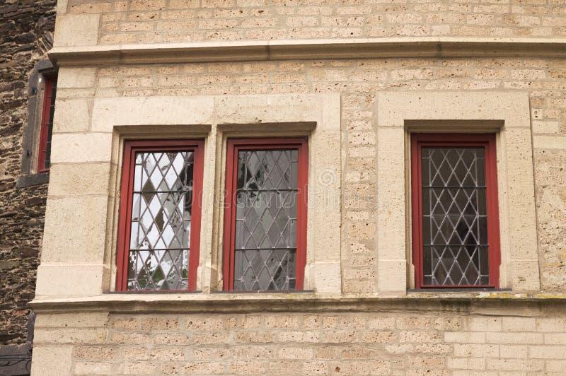 Drie rode vensters in een steenvoorgevel Duitsland royalty-vrije stock foto