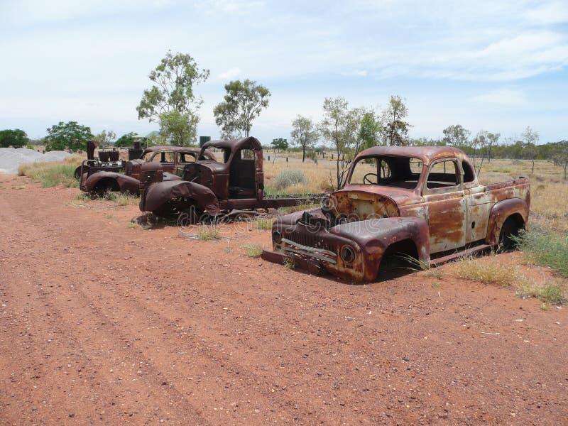 Drie roestende afgedankte wegvoertuigen in het binnenland stock foto's