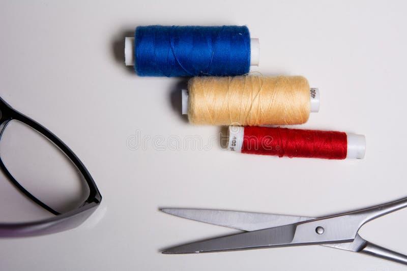Drie rollen van multicolored draden, glazen en schaar stock afbeeldingen