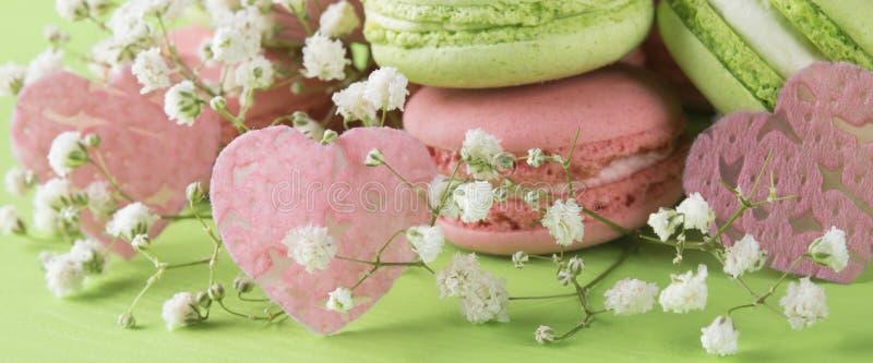 Drie roze harten, valentijnskaarten op een lange achtergrond van groene koekjes royalty-vrije stock afbeeldingen