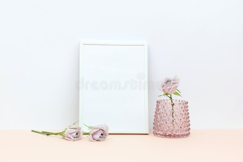 Drie roze rozen op het bureau en het witte kader royalty-vrije stock foto