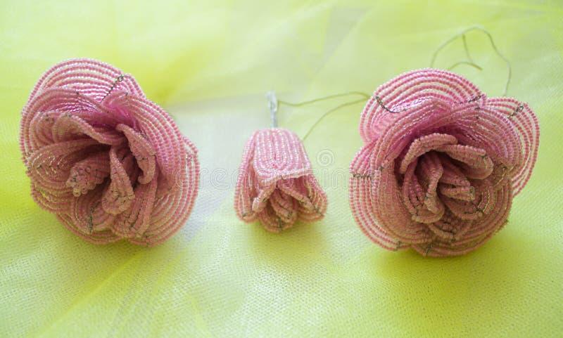 Drie rozen die van parels, roze, twee knoppen en een bloem worden gemaakt Op een gele vage achtergrond royalty-vrije stock foto's