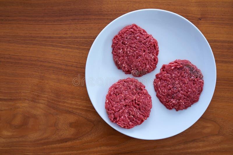 Drie Ruwe Rundvleeslapjes vlees op een Witte Plaat op een Houten Lijst royalty-vrije stock fotografie