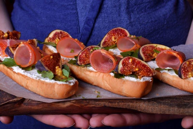 Drie sandwiches met fig., gerookte ham, arugula en zachte kaas op een houten raad stock afbeelding