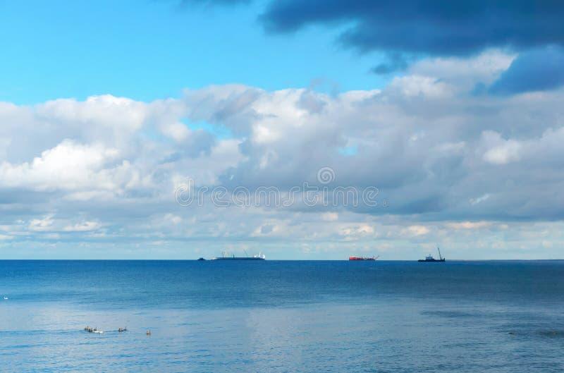 Drie schepen op de horizon stock afbeeldingen