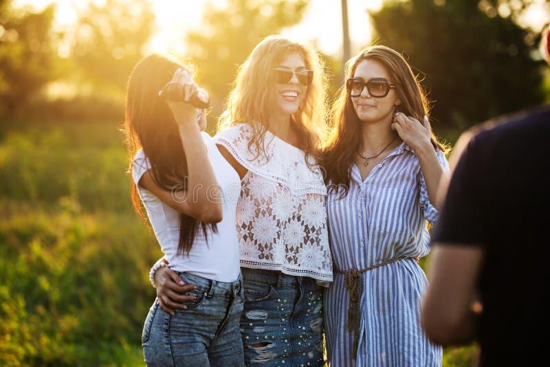 Drie schitterende donker-haired jonge vrouwen in zonnebril gekleed in de mooie kleren stellen openlucht op een zonnige dag royalty-vrije stock foto's