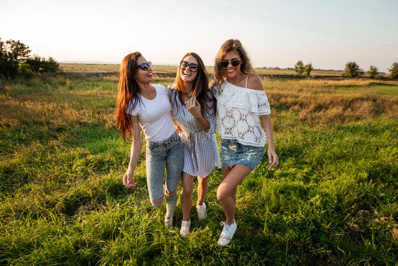 Drie schitterende jonge vrouwen in zonnebril kleedden zich in de mooie klerentribune op het gebied en het glimlachen op een zonni royalty-vrije stock afbeeldingen