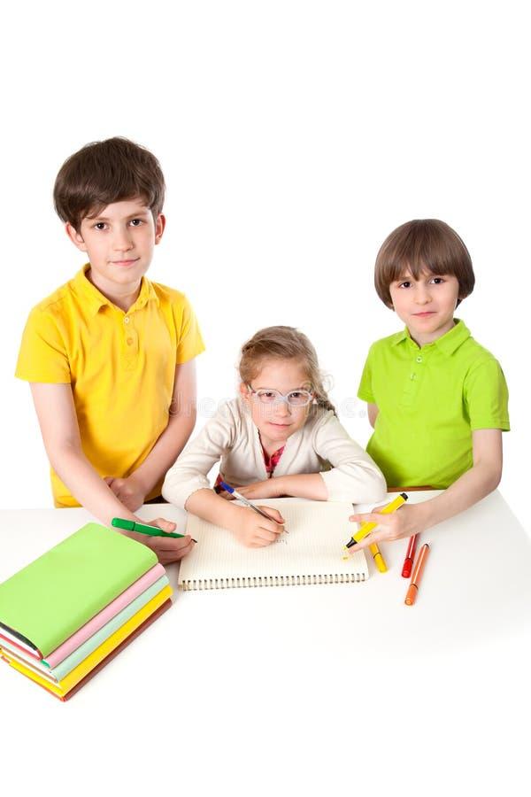 Drie schoolkinderen trekken in het notitieboekje royalty-vrije stock foto