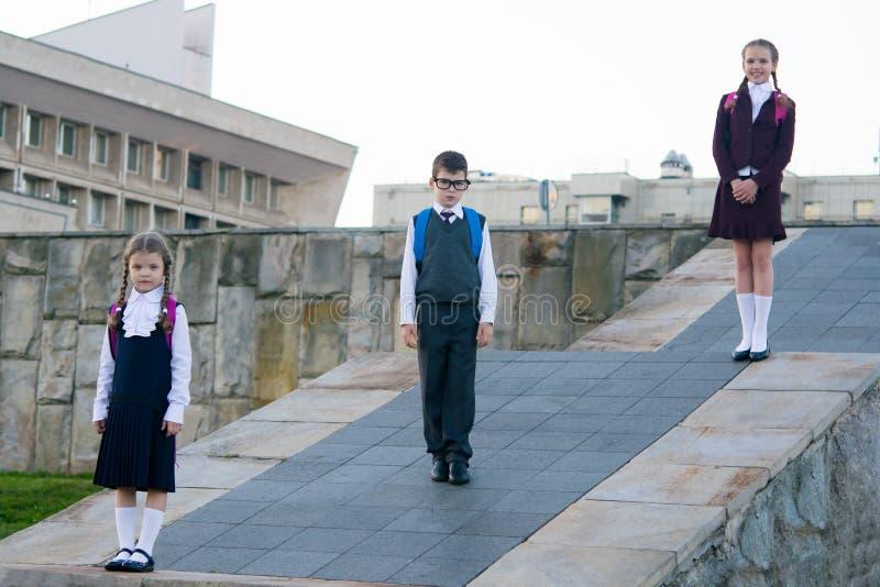 Drie schoolkinderen van verschillende leeftijden, tribune met rugzakken achter hun rug, in schooluniformen stock afbeelding