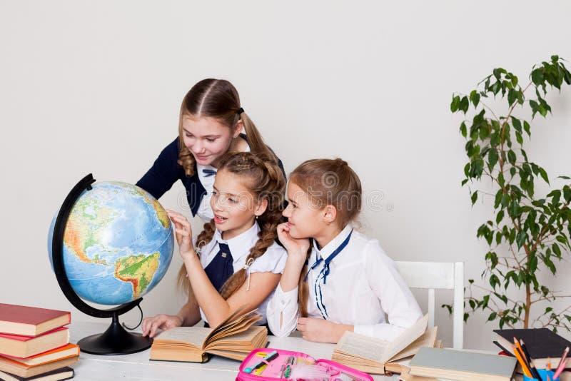 Drie schoolmeisjesmeisjes leren de les van de wereldaardrijkskunde op de kaart stock fotografie