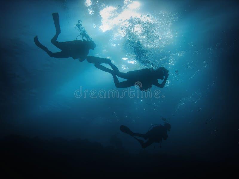 Drie silhouetten van scuba-duiker op de zon en de blauwe waterachtergrond royalty-vrije stock foto