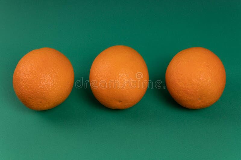 Drie sinaasappelen op een groene achtergrond royalty-vrije stock foto