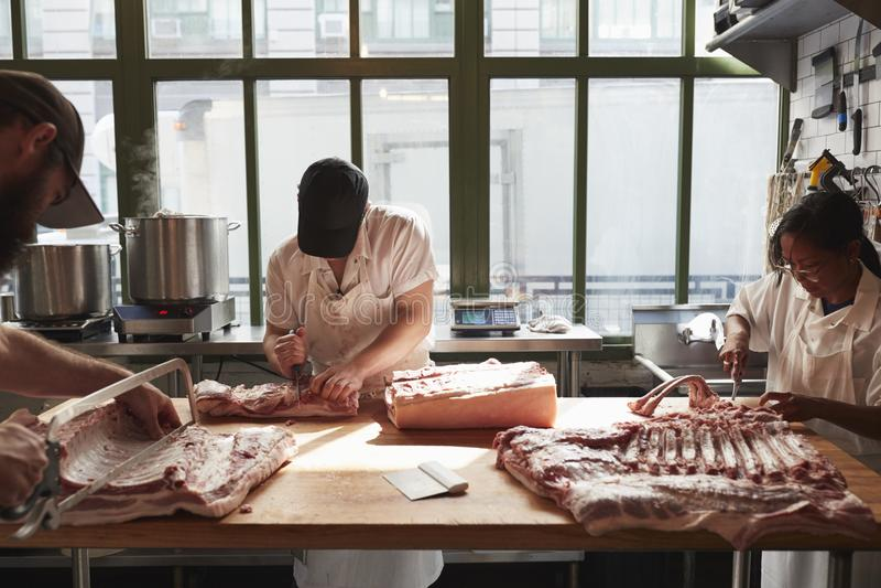 Drie slagers die varkensvlees voorbereiden bij een slagerij stock afbeeldingen