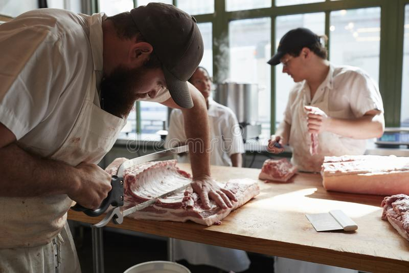 Drie slagers die vlees, besnoeiingen van vlees in slagerij, cl voorbereiden royalty-vrije stock fotografie