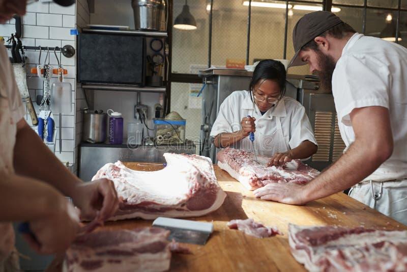 Drie slagers die vlees, besnoeiingen voorbereiden van vlees bij een butcher te verkopen royalty-vrije stock afbeeldingen