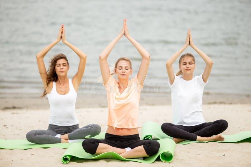 Drie slanke jonge meisjes zitten in een yoga stelt met het sluiten van ogen op matten op zandig strand op een warme dag stock afbeeldingen