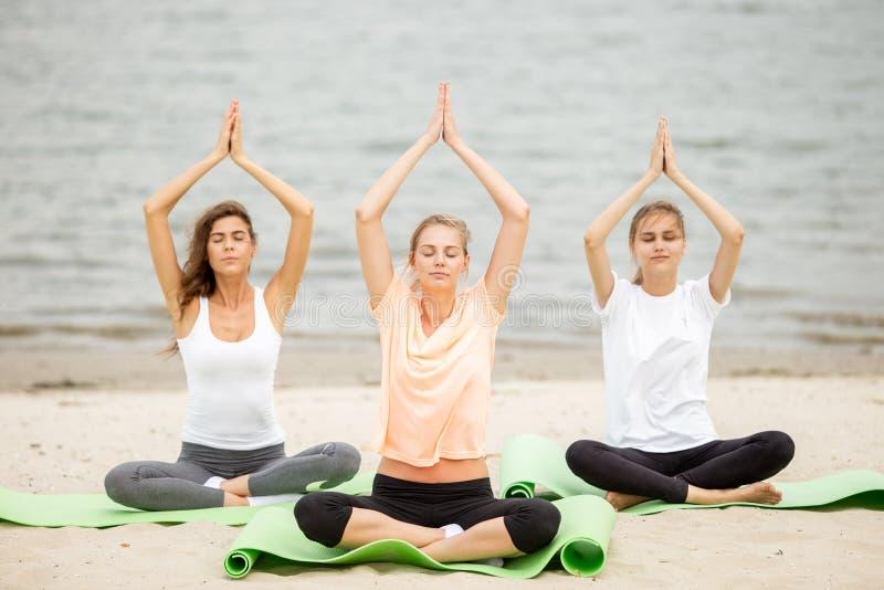 Drie slanke jonge meisjes zitten in een yoga stelt met het sluiten van ogen op matten op zandig strand op een warme dag royalty-vrije stock foto