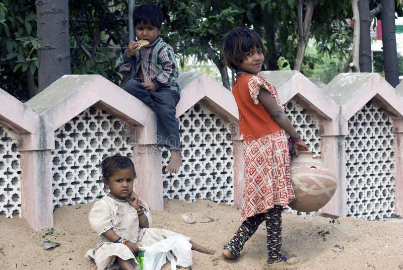 Drie slechte krottenwijkkinderen die op zand spelen stock foto