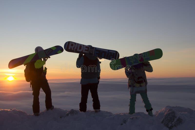 Drie snowboarders die zich bovenop een berg bij dageraad bevinden stock foto