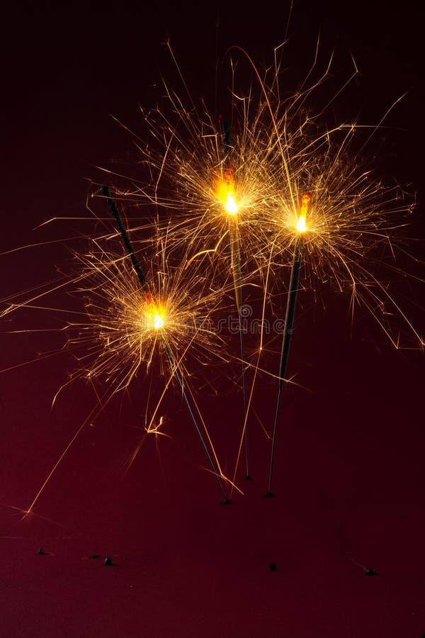 Drie sterretjes die tegen een donkerrode achtergrond, partij branden bedriegen royalty-vrije stock afbeeldingen