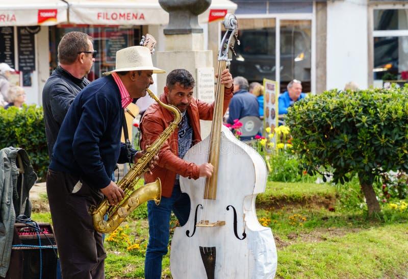 Drie straatmusici die voor toeristen spelen stock afbeelding