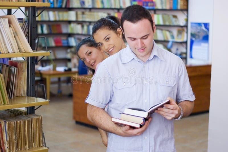 Drie studenten in bibliotheek stock fotografie