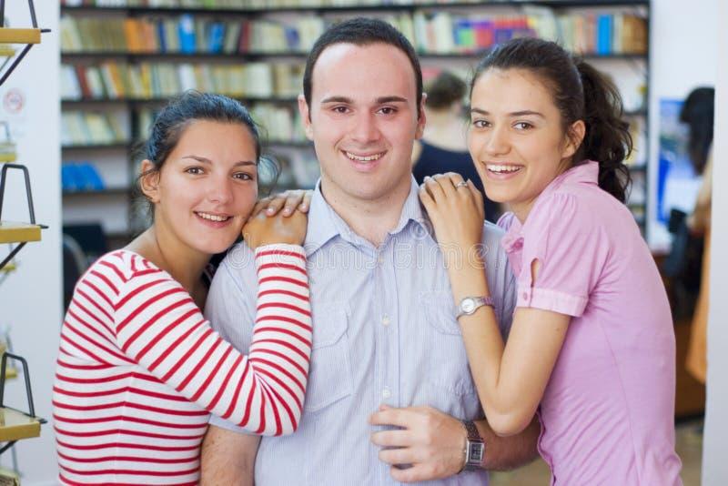 Drie studenten in bibliotheek royalty-vrije stock foto