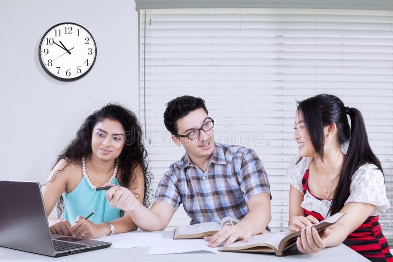 Drie studenten bij woonkamer royalty-vrije stock foto's