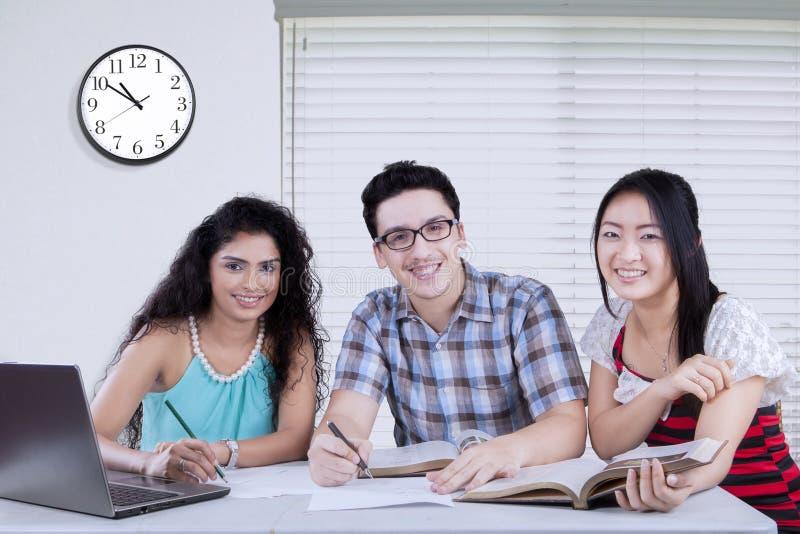 Drie studenten die artikel maken royalty-vrije stock afbeelding