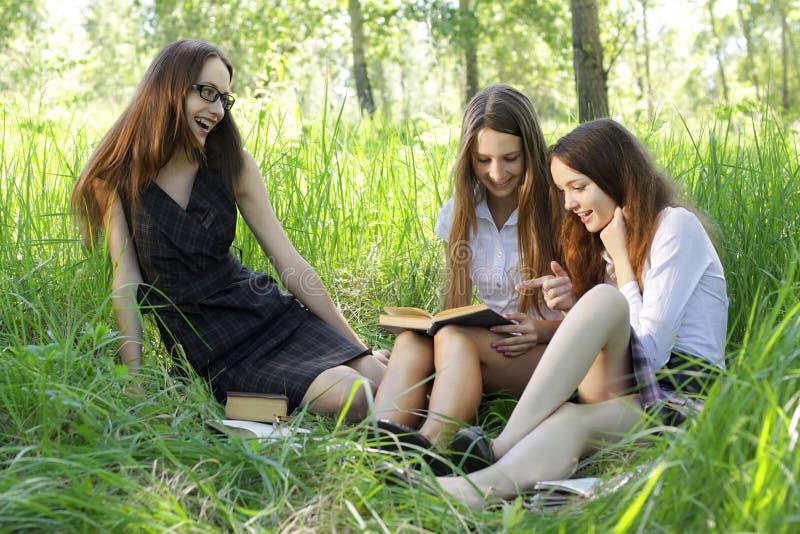 Drie studenten die boeken lezen openlucht stock afbeelding